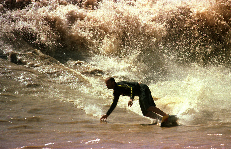 """Surfer Picuruta Salazar participates in the """"I Pororoca Surf Challenge"""" on the tidal bore wave, known as pororoca, in the Araguari River of Brazil's Amazonian state of Amapa. Six reknown Brazilian surfers battled the wave in two elimination heats and one final to see who could surf the wave the longest. The Araguari pororoca is possibly the most feared of all the Amazonian tidal bores, and local residents of the remote areas surrounding the mouth of the river always feared the thunderous waves which capsizes boats and washes away anything in its path twice daily. Thanks to a group of daring surfers, they have begun to see the wave in a different way: as a tourist attraction to generate money in one of the poorest regions of Brazil.(AustralFoto/Douglas Engle)"""