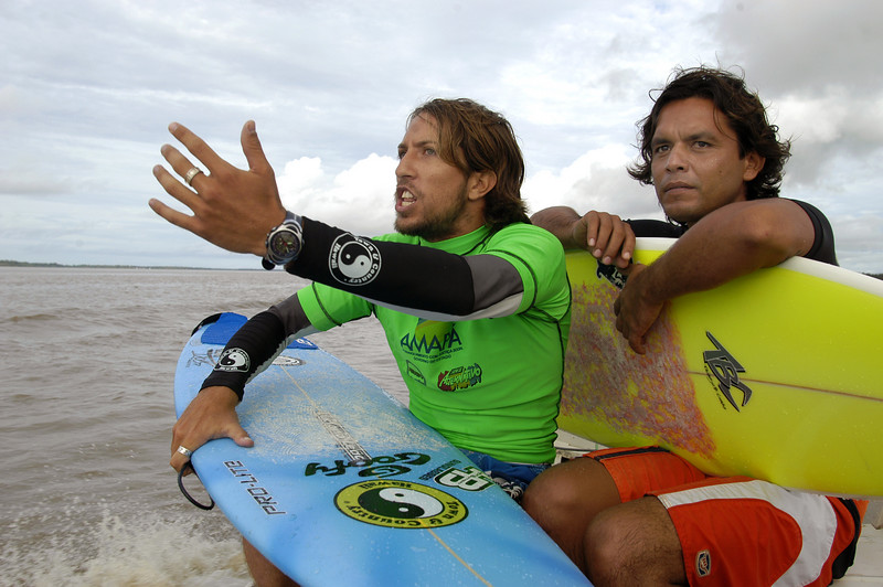"""Brazilian surfer Sergio Laus, left, shouts to fellow surfers on the tidal bore wave, known as pororoca, on the Araguari River. Marcelo Vaia is at right. The Araguari pororoca is possibly the most dangerous of all the Amazonian tidal bores, long feared by locals for wreaking havoc on their communities. wave crests at 2 to 3 meters and races at speeds between 30 to 50 kilometers per hour. To catch it, surfers must leap from a motorboat as the wave barrels upriver. Since the wave only occurs twice per day when the incoming ocean tide reverses the river flow for a time, there are not many chances to catch it, The name """"pororoca"""" comes from an Amazonian indigenous dialect meaning """"destroyer"""" or """"great blast."""" Since time immemorial, people have feared the roar which precedes the wall of water that capsizes boats and washes away anything in its path. (Douglas Engle/Australfoto)"""