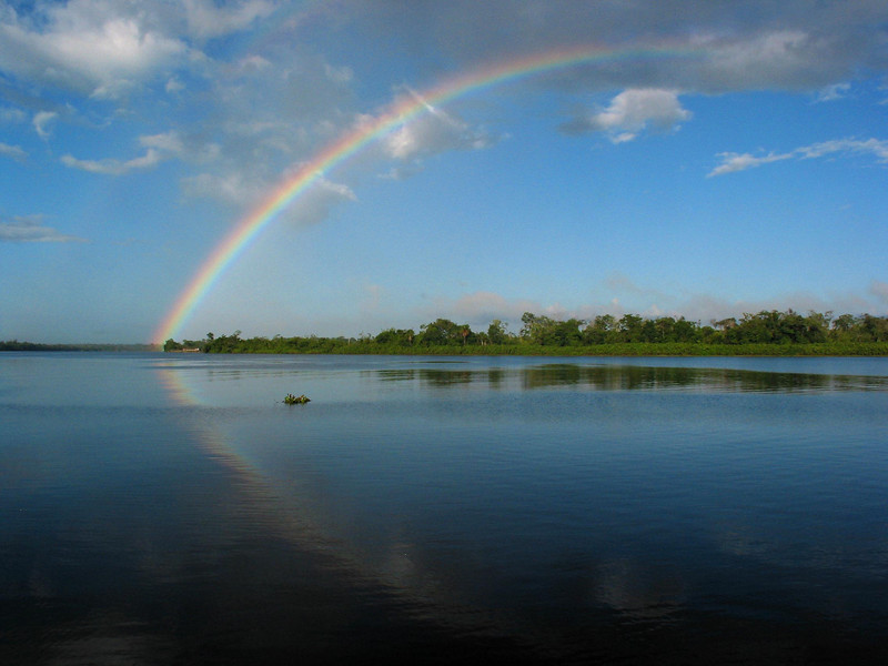 """A rainbow falls on the Araguari River, near Cutias, in Brazil's Amazonian state of Amapa.  Six reknown Brazilian surfers participated in the """"I Pororoca Surf Challenge"""" on the tidal bore wave, known as pororoca, in the river in two elimination heats and one final to see who could surf the wave the longest. The Araguari pororoca is possibly the most feared of all the Amazonian tidal bores, and local residents of the remote areas surrounding the mouth of the river always feared the thunderous waves which capsizes boats and washes away anything in its path twice daily. Thanks to a group of daring surfers, they have begun to see the wave in a different way: as a tourist attraction to generate money in one of the poorest regions of Brazil.(AustralFoto/Douglas Engle)"""