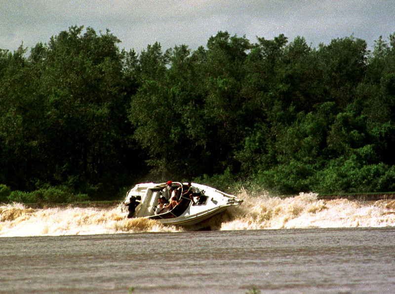 A boat is almost capsized by the approaching tidal bore wave, known as pororoca, in the Mearim River in Brazil's amazonian state of Maranhao. The Mearim pororoca is one of many Amazonian tidal bores which surfers have begun to take on in a quest for adventure and to help local economies in one of the poorest regions of Brazil.  (AustralFoto/Douglas Engle)