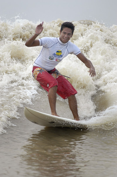 """Brazilian surfer Adilton Mariano surfs on the tidal bore wave, known as pororoca, on the Araguari River, in Brazil's northern state of Amapa. The Araguari pororoca is possibly the most dangerous of all the Amazonian tidal bores, long feared by locals for wreaking havoc on their communities. wave crests at 2 to 3 meters and races at speeds between 30 to 50 kilometers per hour. To catch it, surfers must leap from a motorboat as the wave barrels upriver. Since the wave only occurs twice per day when the incoming ocean tide reverses the river flow for a time, there are not many chances to catch it, The name """"pororoca"""" comes from an Amazonian indigenous dialect meaning """"destroyer"""" or """"great blast."""" Since time immemorial, people have feared the roar which precedes the wall of water that capsizes boats and washes away anything in its path. Now, however, the people are less fearful and have begun to see the wave as a potential tourist attraction that could generate money in the state of one of the poorest of Brazil.(Douglas Engle/Australfoto)"""