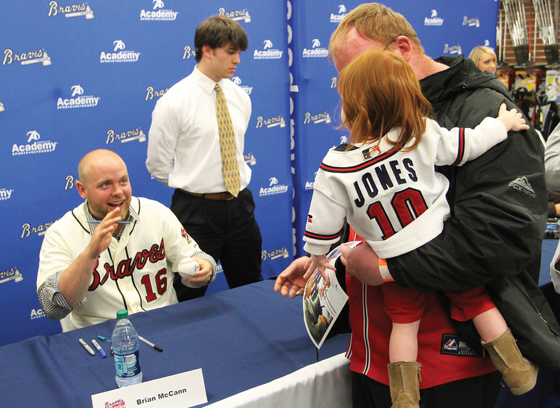 Atlanta Braves catcher Brian McCann greets a fan during the club's promotional tour prior to the 2012 season.