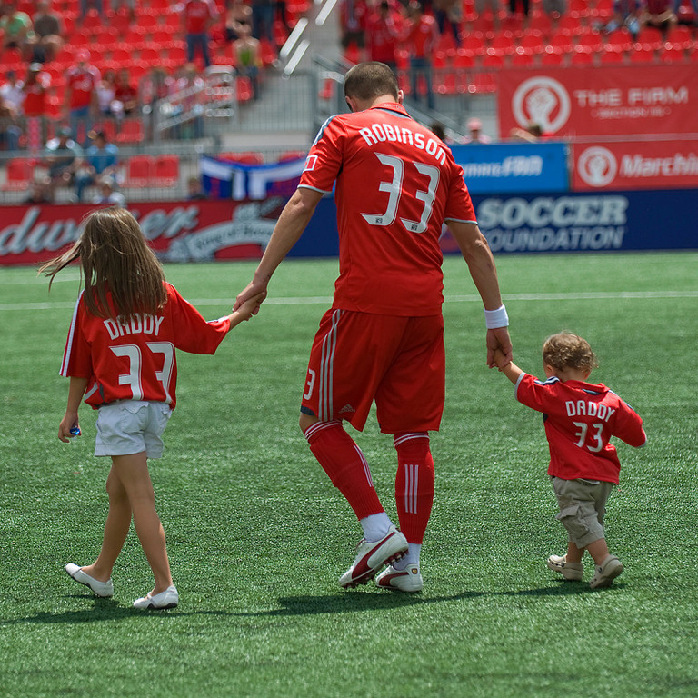 18-July 2009: Toronto FC midfielder Carl Robinson #33 takes the pitch with his kids at the beginning of a game between the Toronto FC and the Houston Dynamo at BMO Field in Toronto.