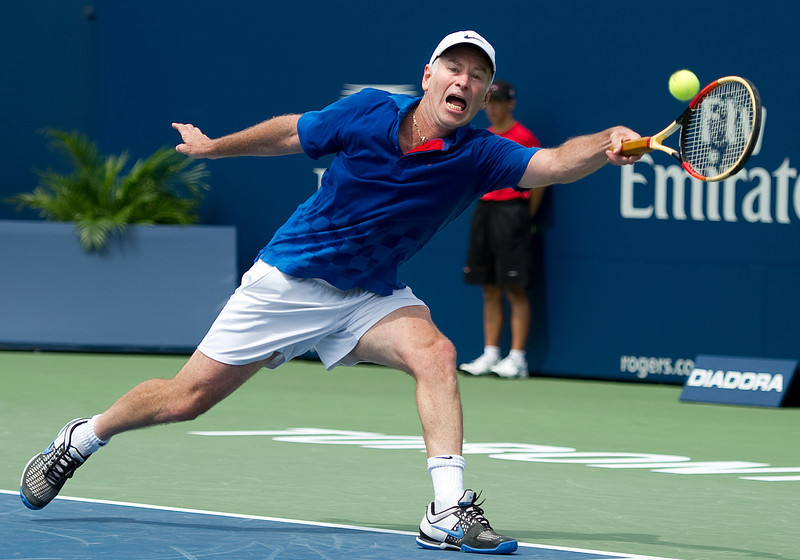 August 13 2011: John McEnroe of USA reaches for a ball and injures himself  during the Rogers Legends Cup at the 2011 Rogers Cup at the Rexall Centre in Toronto, Ontario Canada.<br /> The match was called due to John McEnroe's injury.