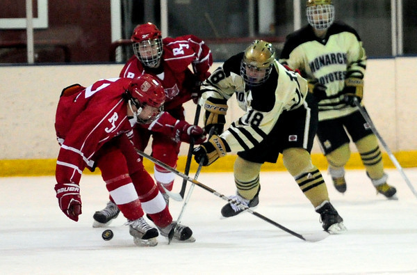 Monarch's David Neitenbach (right) hits the puck away from Regis' Brian Engh (led) during their hockey game in Superion, Colorado February 11, 2013. BOULDER DAILY CAMERA/ Mark Leffingwell
