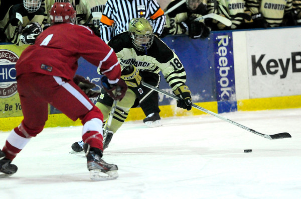 Monarch's David Neitenbach (right) hits the puck away from Regis' Brady Hall (left) during their hockey game in Superion, Colorado February 11, 2013. BOULDER DAILY CAMERA/ Mark Leffingwell