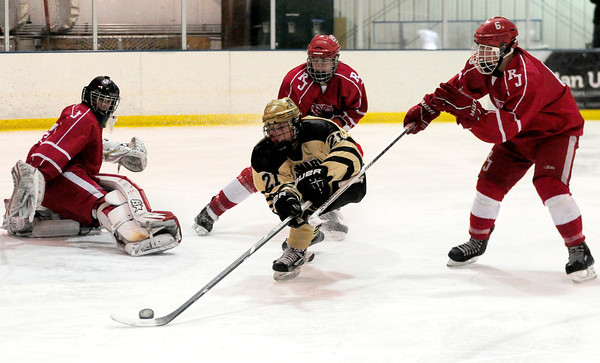 Monarch's Jake Christofferson (front) tries to slide the puck by Regis' goalie #35 (left)(not on roster), Nolan Carothers (back middle) and Carter Alcock (right) during their hockey game in Superion, Colorado February 11, 2013. BOULDER DAILY CAMERA/ Mark Leffingwell