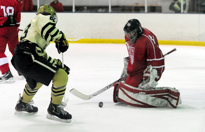 Monarch's Gian Cervo (left) takes a shot on Regis' goalie #35 (not on roster Right) during their hockey game in Superion, Colorado February 11, 2013. BOULDER DAILY CAMERA/ Mark Leffingwell