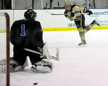 Monarch's Joey Buchan (right) takes a shot on Columbine's Charlie Marchese (left) during their hockey game in Superior , Colorado February 4, 2013. BOULDER DAILY CAMERA/ Mark Leffingwell
