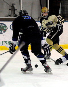 Monarch's Justin White (right) takes a shot between the legs of  Columbine's Logan Seibold (left) during their hockey game in Superior , Colorado February 4, 2013. BOULDER DAILY CAMERA/ Mark Leffingwell