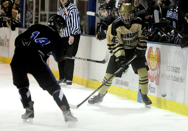 Monarch's Max Legere (right) hits the puck past Columbine's Ian Lewis (left) during their hockey game in Superior , Colorado February 4, 2013. BOULDER DAILY CAMERA/ Mark Leffingwell