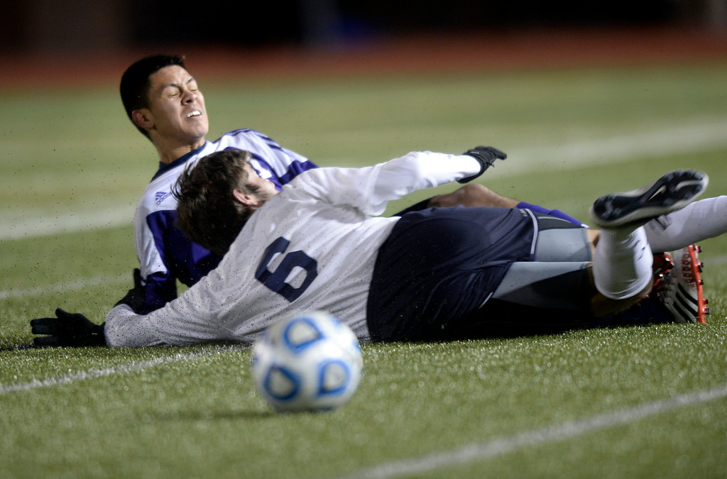. Boulder High School\'s Brian Castruita, left, goes down after a slide tackle by Aaron Haefner during a semi-final game against Pine Creek High School on Wednesday, Nov. 6, at Cherokee Trail High School in Aurora. Boulder lost the game 1-0. For more photos of the game go to www.dailycamera.com Jeremy Papasso/ Camera