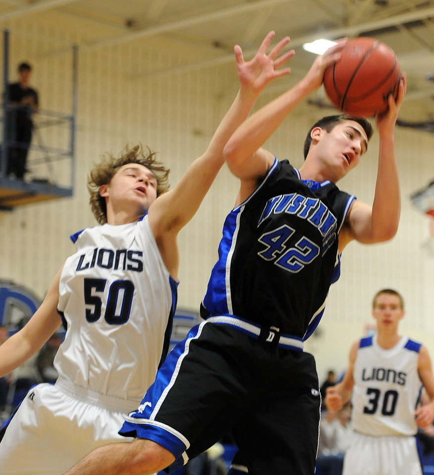 """Shawn O'Grady of Dawson gets a rebound over Macrae Falce (50)  of Lyons on Saturday.<br /> For more photos of the game go to  <a href=""""http://www.dailycamera.com"""">http://www.dailycamera.com</a>.<br /> Cliff Grassmick / January 26, 2013"""
