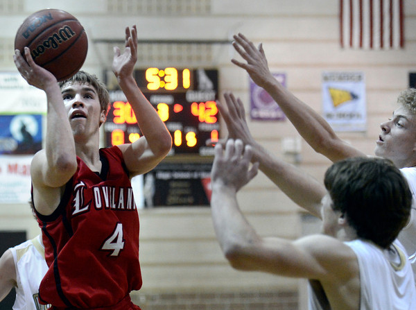 """Loveland High School's Brian Strasbaugh takes a shot over Monarch High School's Jay Macintyre, center, and Erik Lawson, right, during a game on Tuesday, Feb. 5, at Monarch High School in Louisville. For more photos of the game go to  <a href=""""http://www.dailycamera.com"""">http://www.dailycamera.com</a><br /> Jeremy Papasso/ Camera"""