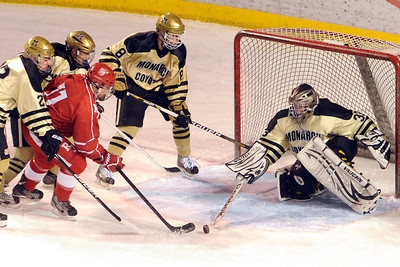 Monarch High School goalie Ian Oden deflects a shot by Regis Jesuit's Kirk Underwood (11) while Monarch's Alec Michaels, left, David Neitenbach and Chris Miller look on in the first period of their game on Thursday, Feb. 28, 2013 at Magness Arena on the University of Denver campus.