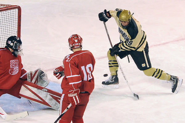 Monarch High School's Alex Barber, right, takes a shot on Regis Jesuit goalie Sam Harden while Logan Baca looks on in the first period of their game on Thursday, Feb. 28, 2013 at Magness Arena on the University of Denver campus.