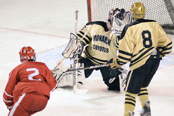 Monarch High School goalie Ian Oden makes a glove save while teammate Chris Miller (8) and Regis Jesuit's Sean Brennan look on in the first period of their game on Thursday, Feb. 28, 2013 at Magness Arena on the University of Denver campus.