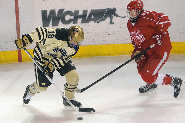 Monarch High School's David Neitenbach, left, and Regis Jesuit's Conner Wigton go after the puck in the first period of their game on Thursday, Feb. 28, 2013 at Magness Arena on the University of Denver campus.