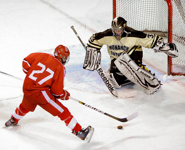 DENVER, CO. - FEBRUARY 28: Raiders forward Connor Brennan (27) pressured Monarch goalie Ian Oden (33) in the first period. Monarch High School met Regis Jesuit Thursday night, February 28, 2013 in a semifinal match in the Colorado State Ice Hockey Championships at Magness Arena in Denver.  (Photo By Karl Gehring/The Denver Post)