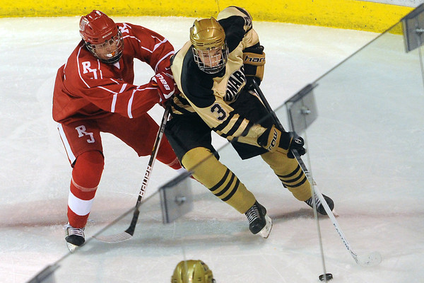 Monarch High School defenseman Tim Morton, right, battles along the boards with Regis Jesuit's Brian Engh in the first period of their game on Thursday, Feb. 28, 2013 at Magness Arena on the University of Denver campus.