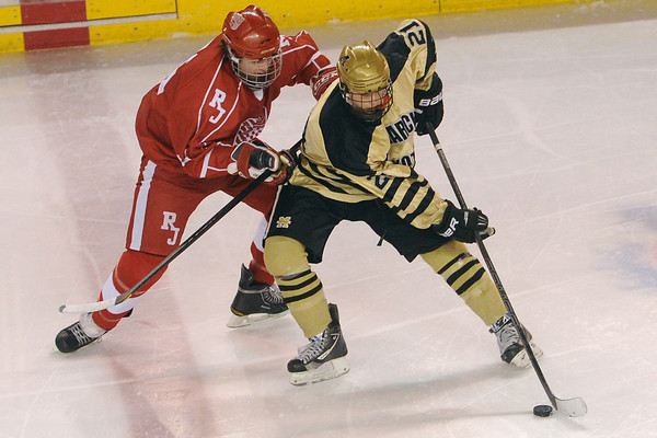 Monarch High School forward Jake Christofferson, right, tracks down the puck in front of Regis Jesuit defenseman Nolan Carothers in the first period of their game on Thursday, Feb. 28, 2013 at Magness Arena on the University of Denver campus.