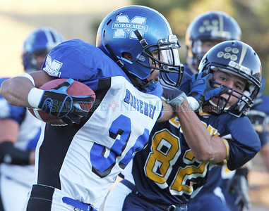 (34) Russell Disch of St. Michael's High School holds off Santa Fe High's (82) Moses Montoya during the first quarter of a football game in Santa Fe, N.M. on Sept. 25, 2009. ©Natalie Guillen/The New Mexican