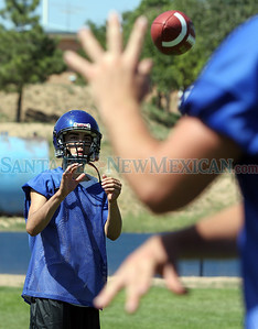 (L-R) Josh Roybal reaches to catch a pass from Michael Wiegel during a St. Michael's High School football practice in Santa Fe, N.M. on Aug. 10, 2009. ©Natalie Guillen/The New Mexican