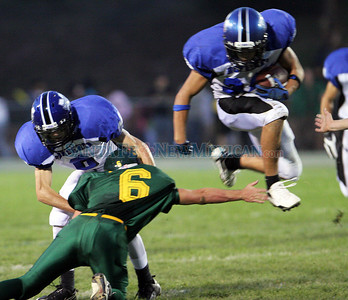 St. Michael's (8)(L) Brendan Mahan blocks (6) Ryan Schleft of Los Alamos High School as (34)(R) Russell Disch rushes past in the second quarter of a football game in Los Alamos, N.M. on Aug. 4, 2009. ©Natalie Guillen/The New Mexican