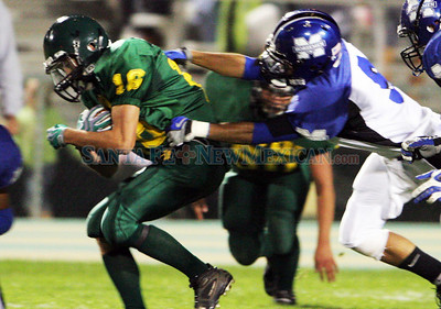 Andre Salazar (R)(9) of St. Michael's High School brings down Mike Sanchez (16) of Los Alamos High School during the fourth quarter of a football game in Los Alamos, N.M. on Aug. 4, 2009. ©Natalie Guillen/The New Mexican