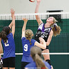 Julia Bennett spikes the ball over the Houghton Academy defenders, Friday, Oct. 27.
