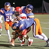Desmond Battin (left), Dominic Ferlito (back) and Will Rogers (front) work together to tackle a Pal-Mac player, Friday, Sept. 1.