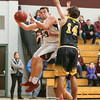 Austin Gibson works under the basket to pass the ball to a teammate in the game with South Seneca.