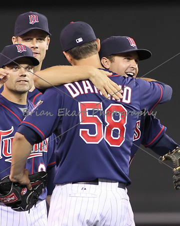 Minnesota Twins infielder Brian Dozier (20) hugs Minnesota Twins pitcher Scott Diamond (58) while Minnesota Twins infielder Jamey Carroll (8) and Minnesota Twins infielder Justin Morneau (33) look on after pitching a complete game shutout on July 27, 2012:  during the Minnesota Twins game versus the Cleveland Indians at Target Field in Minneapolis, MN.