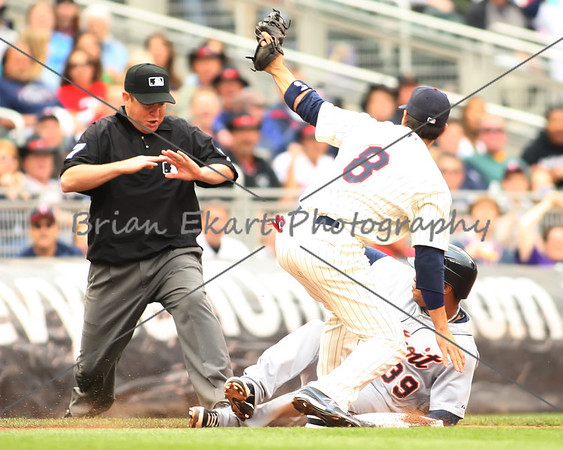 Minnesota Twins infielder Jamey Carroll (8) shows the ball to the umpire after applying the tag to Detroit Tigers infielder Ramon Santiago (39), he was called safe at third on May 26, 2012:  during the Minnesota Twins game versus the Detroit Tigers at Target Field in Minneapolis, MN.