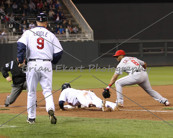 Minnesota Twins infielder Jamey Carroll (8) dives back to third base while Los Angeles Angels infielder Kendrys Morales (8) applies the tag on May 8, 2012:  at the Minnesota Twins game versus the Los Angeles Angels of Anaheim at Target Field in Minneapolis, MN.