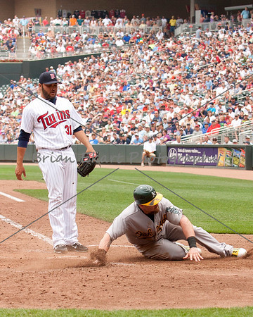 Oakland Athletics outfielder Jonny Gomes (31) slides safely home during a wild pitch by Minnesota Twins pitcher Alex Burnett (31) during the game on July 15, 2012:  during the Minnesota Twins game versus the Oakland Athletics at Target Field in Minneapolis, MN.