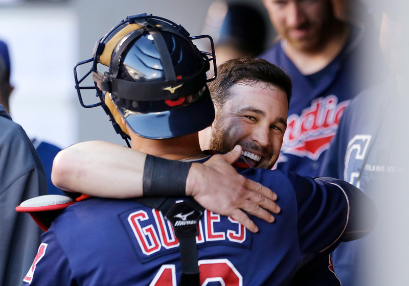 Cleveland Indians' Jason Kipnis, right, is hugged by catcher Yan Gomes after scoring against the Seattle Mariners in the first inning of a baseball game Tuesday, July 23, 2013, in Seattle. (AP Photo/Elaine Thompson)