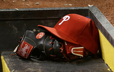617e1a19ce6 A Philadelphia Phillies hat and glove rest on a step leading into the dugout  in a