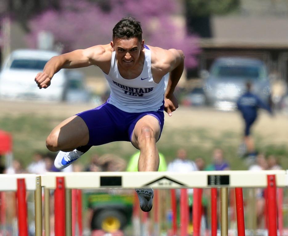 . Mountain View\'s Nolan Kembel leaps a hurdle during the R2J Invite on Thursday April 13, 2017 in Loveland. (Cris Tiller / Loveland Reporter-Herald)