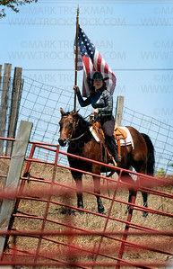 The woman holding the Stars & Stripe while astride her horse would later sing our national anthem at the Hamel Rodeo on Saturday, July 12 at Corcoran Lions Park.