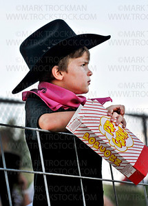 Five year old Jack Robinson, Hanover, takes in the action at the Hamel Rodeo Bull Riding Bonanza, July, 7, at Corcoran Lions Park.  Fans were encouraged to wear pink on Thursday for Tough Enough to Wear Pink. One dollar for every fan in pink will be donated to the Susan G. Komen Foundation for breast cancer research.