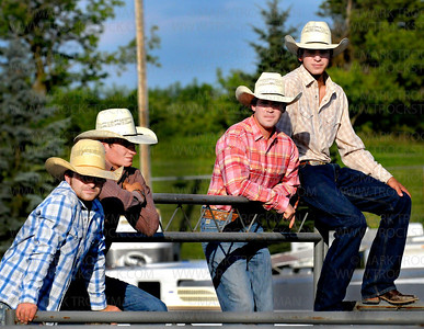 Pro rodeo cowboys check out the action in the animal pens prior to the start of the 31st annual Hamel Rodeo and Bull Riding Bonanza at Corcoran Lions Park Thursday, July 7.  Fans were encouraged to wear pink on Thursday for Tough Enough to Wear Pink. One dollar for every fan in pink will be donated to the Susan G. Komen Foundation for breast cancer research.
