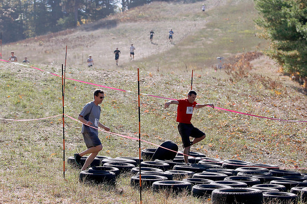 Record-Eagle/Jan-Michael Stump<br /> Saturday's King of the Mountain race at Mt. Holiday featured a three mile course with obstacles ranging from car tires to a water pit. Nearly 120 runners competing in the race, which was held to raise funds for the non-profit ski area.