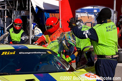 A crewman removes plastic screen from windshield while Nic Jonsson climbs aboard the #31 Ferrari 430 GT