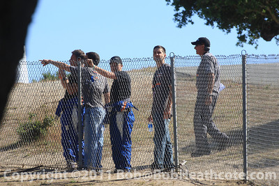 Race team members watch the test session from the Corkscrew at Mazda Raceway Laguna Seca
