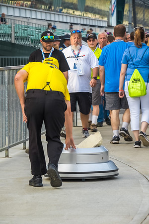 IMS volunteer pushing the Borg-Warner Trophy rolling stand along pit row.