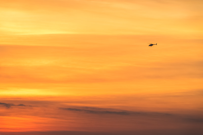 News chopper circling the Indianapolis Motor Speedway in front of a painted sunrise sky on the morning of the 101st Running of the Indy 500.