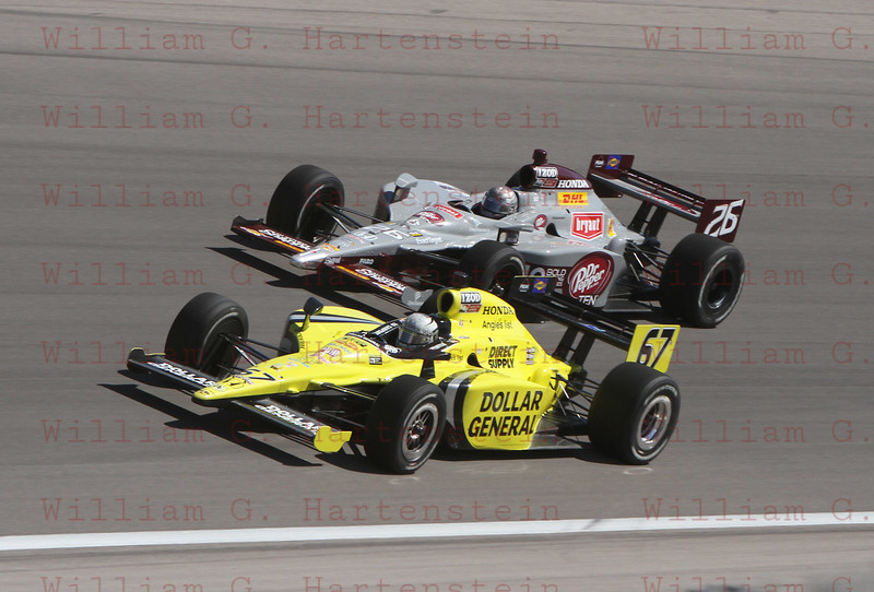 Drivers Ed Carpenter #67 and Marco Andretti #26 battle into Turn 4 at the Las Vegas Indy 300. Oct. 16, 2011