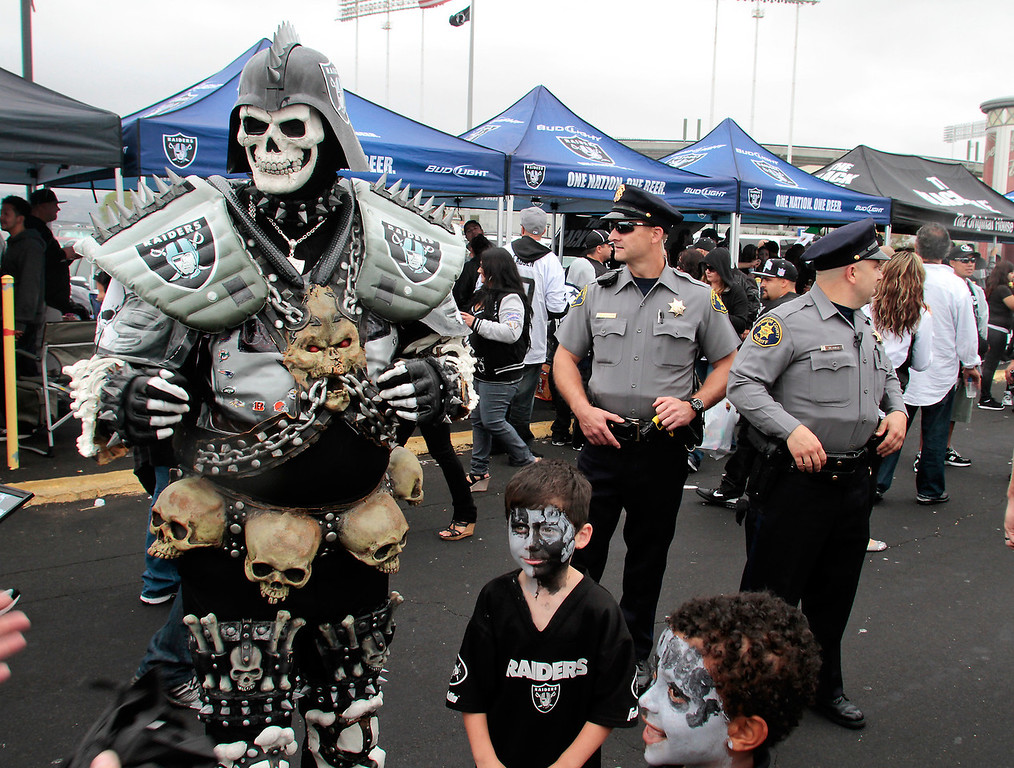 Raiders fans and Alameda County Sherifs share the parking lot before the Raiders-Jets game at the Oakland Coliseum, Calif.,  on Sunday, September 25,  2011.