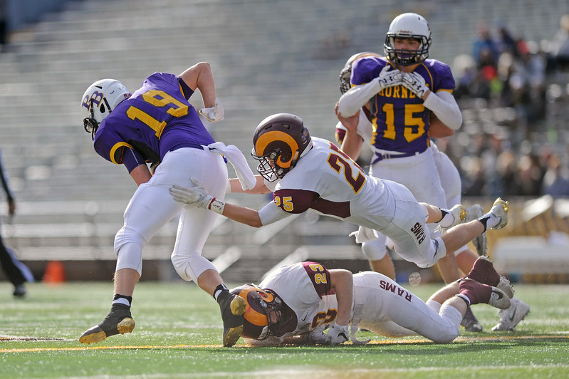 Big Horn's Kade VanDyken (25) and Kade Eisele (23) lunge to bring down Pine Bluffs' Brian Steger during the 1A state championship on Saturday, Nov. 11 at War Memorial Stadium. Mike Pruden | The Sheridan Press